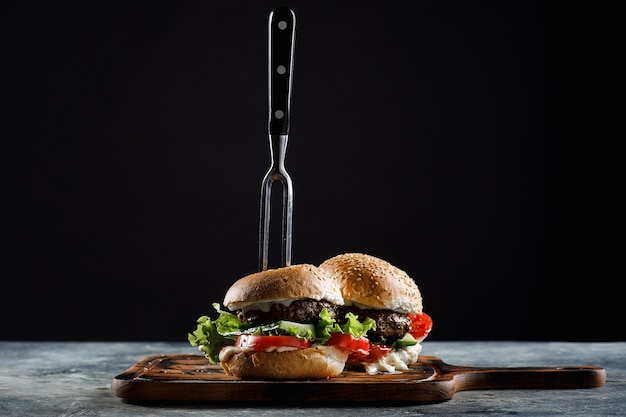 Hamburger met gehaktballen op een zwarte. met een vork vast.