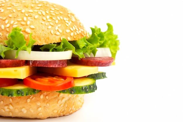 Hamburger met groenten en worst op een witte achtergrond. fastfood en ontbijt. calorieën en dieet.