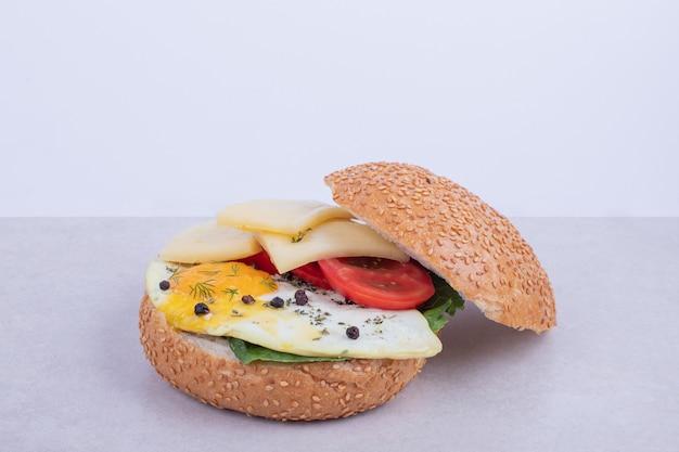 Hamburger met omelet, tomaten, champignons en ui op wit.