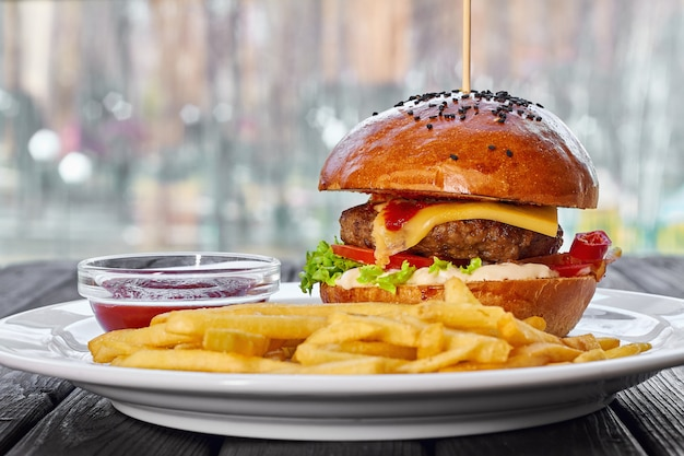 Hamburger met runderkotelet, kaas, patat, tomaat, salade, saus en ketchup
