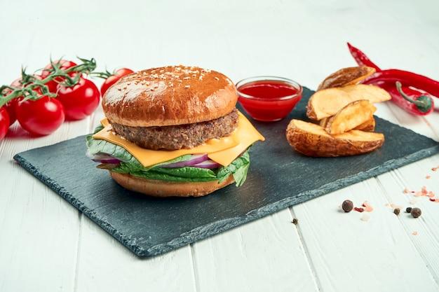 Hamburger met rundvlees, tomaat, gekarameliseerde uien en gesmolten kaas in een zwarte keramische plaat. detailopname. straatvoedsel