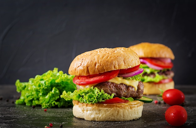 Hamburger met rundvleeshamburger en verse groenten op donkere achtergrond. smakelijk eten.