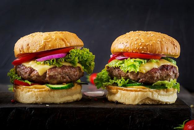 Hamburger met rundvleesvleeshamburger en verse groenten op donkere oppervlakte.