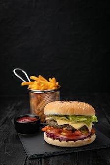 Hamburger met saus en frietjes op een donkere houten tafel