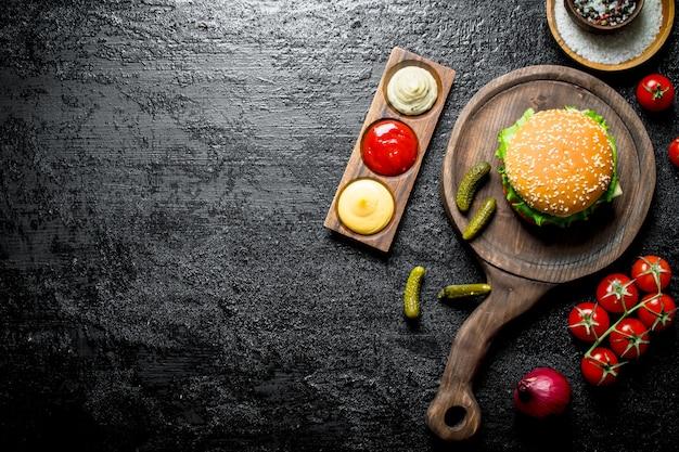 Hamburger met sauzen, tomaten en kruiden op rustieke tafel