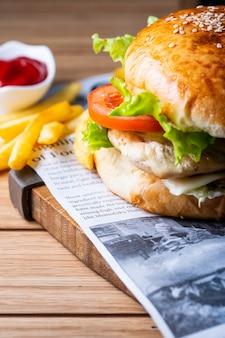 Hamburger met tomaten en sla geserveerd met patat en ketchup