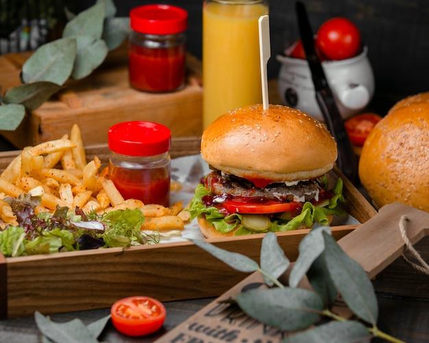 Hamburger met tomatensaus en frietjes in houten dienblad.