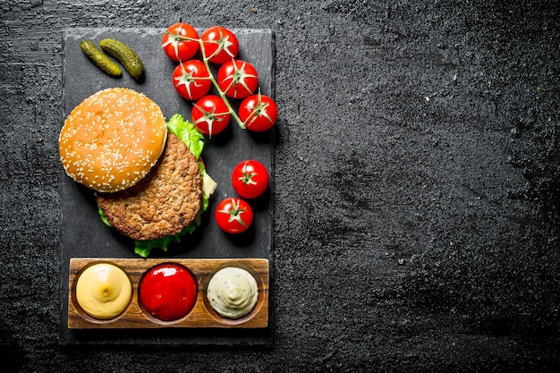 Hamburger op een stenen bord met sauzen en tomaten op een tak op zwarte rustieke tafel.