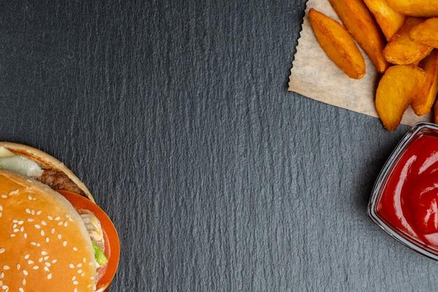 Hamburger op leisteen, zwart stenen servies met rustieke aardappelen en ketchup. bovenaanzicht.