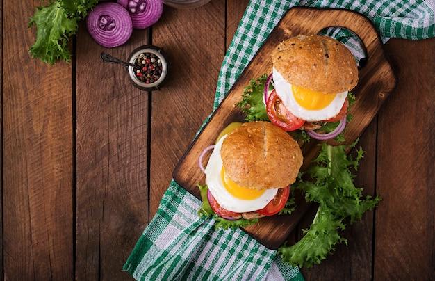 Hamburger (sandwich) met kip burger, sla, tomaat, gebakken ei en tartaarsaus