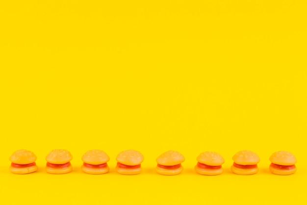 Hamburger-snoepjes op een rij op geel oppervlak