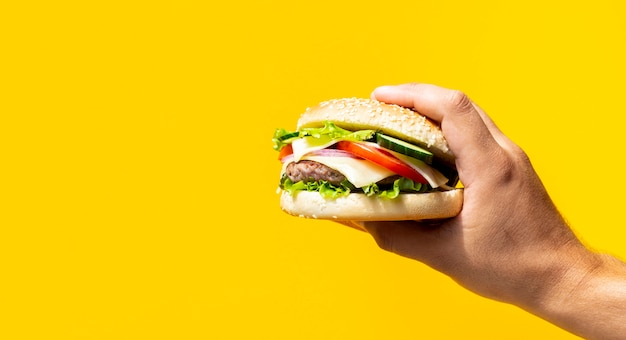 Hamburger voor gele achtergrond wordt gehouden die