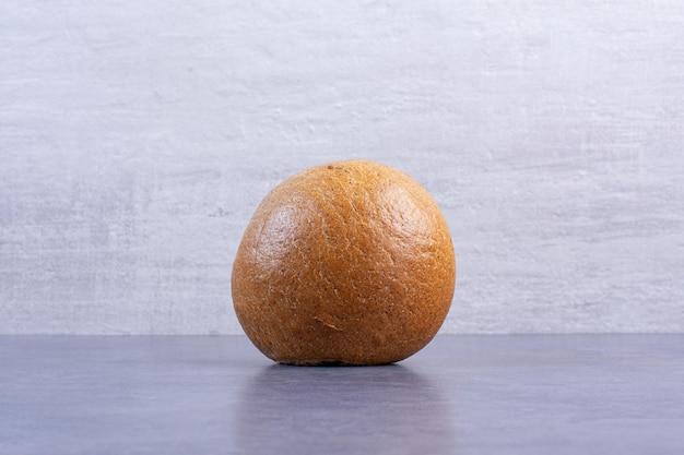 Hamburgerbroodje dat rechtop op marmeren achtergrond staat. hoge kwaliteit foto