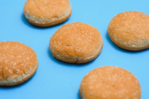 Hamburgerbroodje leeg geïsoleerd. amerikaans voedsel klassiek rond hamburgerbrood dat op een blauwe achtergrond wordt geïsoleerd