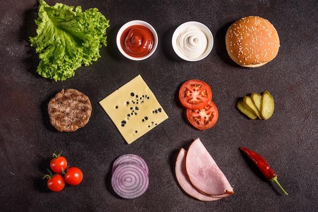 Hamburgeringrediënten op de donkere achtergrond