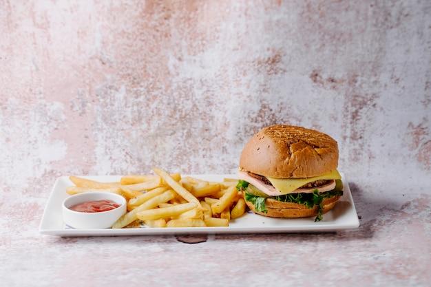 Hamburgermenu met frieten en ketchup binnen witte plaat.
