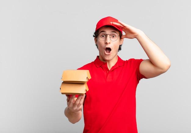 Hamburgers bezorgen jongen die er blij, verbaasd en verrast uitziet, glimlacht en verbazingwekkend en ongelooflijk goed nieuws realiseert
