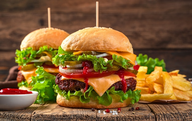 Hamburgers close-up op een bruine achtergrond. fast food. twee sappige hamburgers met vlees, groenten en kaas.