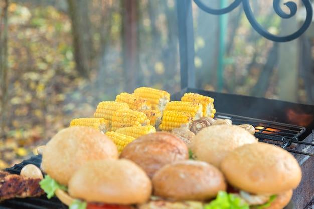 Hamburgers en maïs gekookt buiten op de grill