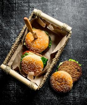 Hamburgers in een mand met een mes. op rustieke achtergrond