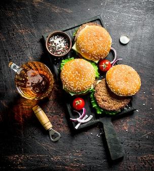 Hamburgers met bier en kruiden. op donkere rustieke achtergrond