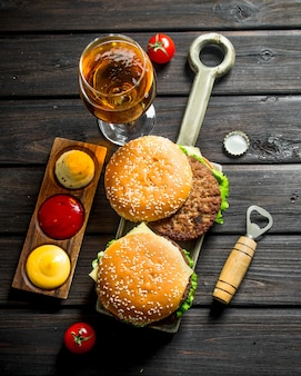 Hamburgers met bier in een glas en verschillende sauzen.