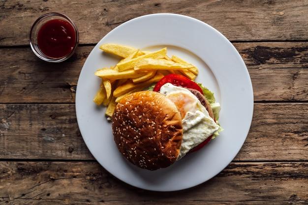 Hamburgers met ei en aardappelen op rustieke houten tafel