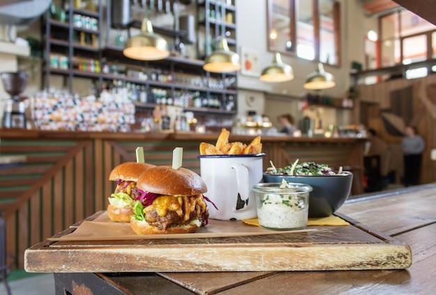 Hamburgers met frietjes in een kopje en saus op een houten dienblad