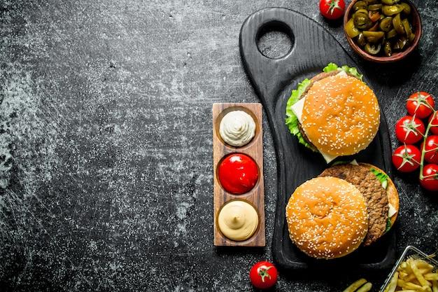 Hamburgers met frietjes, tomaten en jalapenos in kom op rustieke tafel