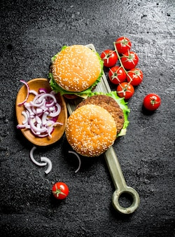 Hamburgers met gehakte uien in kom en kersen. op zwarte rustieke achtergrond