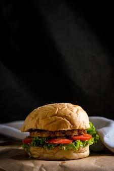 Hamburgers met kaas, salades en groenten op een zwarte ruimte