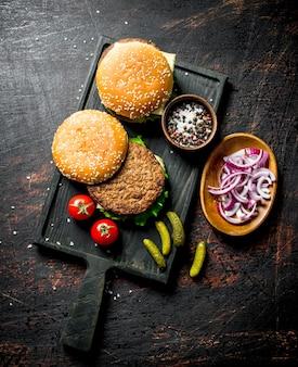 Hamburgers met kruiden en gehakte uien in kommen op rustieke tafel