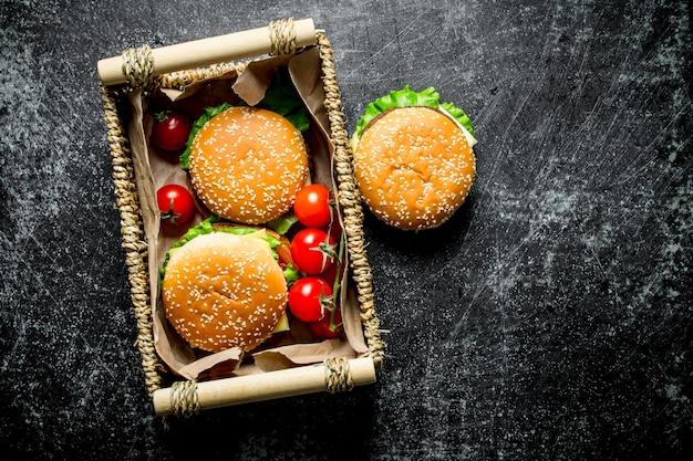 Hamburgers met rundvlees en groenten in de mand. op zwarte rustieke achtergrond