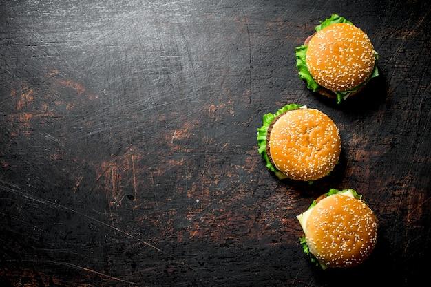 Hamburgers met rundvlees en groenten op donkere rustieke tafel.