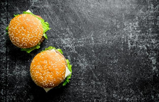 Hamburgers met rundvlees en groenten. op zwarte rustieke achtergrond