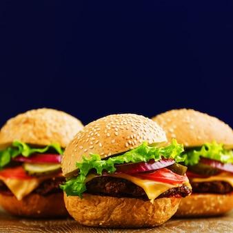 Hamburgers met rundvlees, tomaat, kaas en ui op rustieke tafel