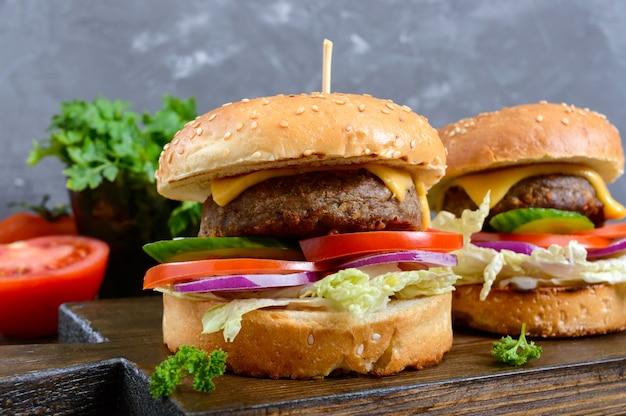 Hamburgers met sappige kotelet, verse groenten, krokant broodje met sesamzaadjes op een houten tafel. detailopname. traditioneel fastfood.