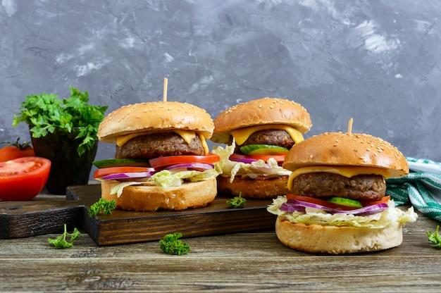 Hamburgers met sappige kotelet, verse groenten, krokant broodje met sesamzaadjes op een houten tafel. traditioneel fastfood.