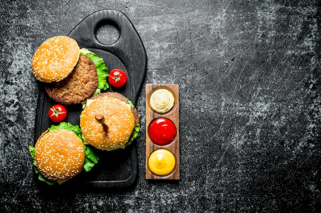 Hamburgers met slablaadjes, tomaten en sauzen. op zwarte rustieke achtergrond