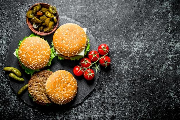 Hamburgers met tomaten en augurken op stenen bord op zwarte rustieke tafel