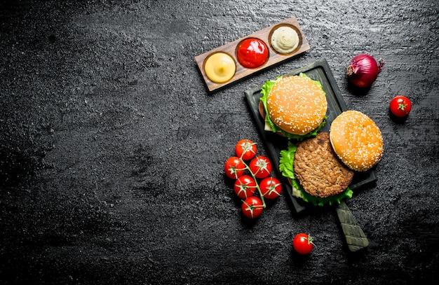 Hamburgers met tomaten, sauzen en uien op rustieke tafel