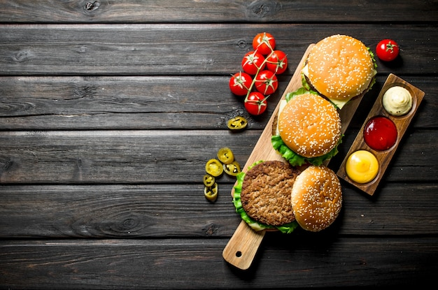 Hamburgers met verschillende sauzen, jalapenos en tomaten op zwarte houten tafel