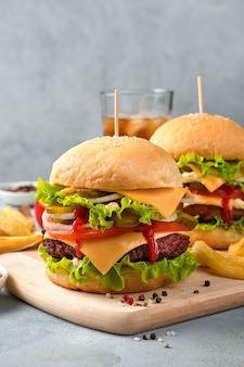 Hamburgers met vlees, kaas en groenten op de achtergrond van cola en frietjes. verticale weergave. fast food.