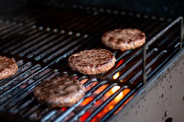 Hamburgers op de grill met dansende vlammen tot in de perfectie bereid. rundvlees of varkensvlees barbecue hamburgers voor hamburger bereid gegrild op bbq vuurvlam grill. bereiding van een partij runderpasteitjes
