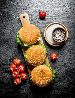 Hamburgers op een houten standaard met kruiden en tomaten op rustieke tafel