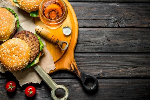 Hamburgers op papier met bier en tomaten op rustieke tafel