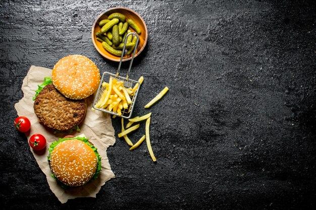 Hamburgers op papier met frietjes, augurken en tomaten op rustieke tafel