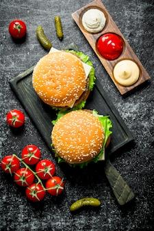 Hamburgers op snijplank en verschillende sauzen op rustieke tafel