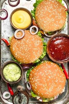 Hamburgers van vers rundvlees en groenten met verschillende sauzen op een stalen plaat. op een rustieke ondergrond.