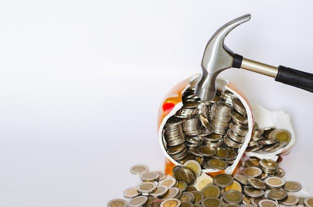 Hamer breken spaarvarken met thaise baht munten op witte achtergrond